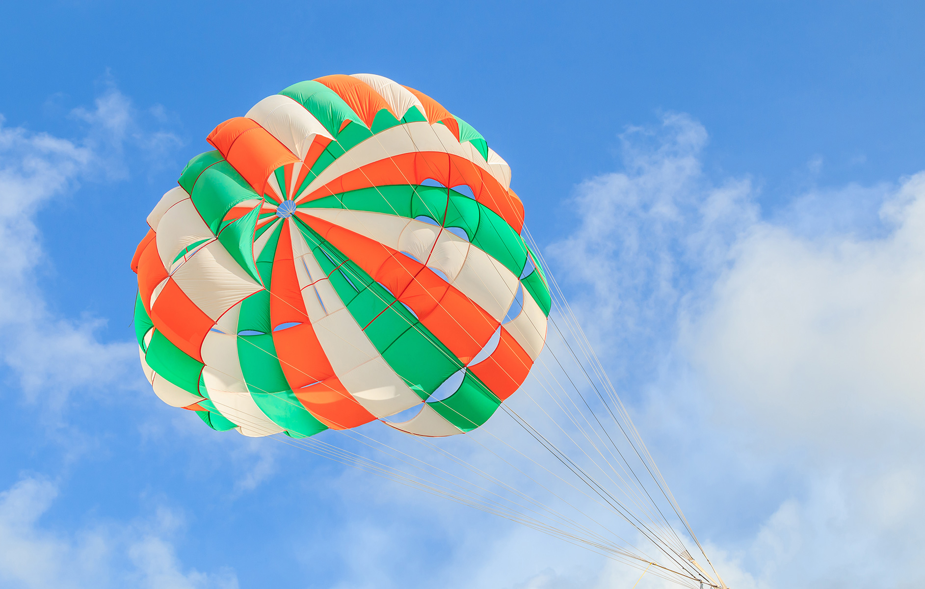 Orange, green, and white parasail against a blue sky.